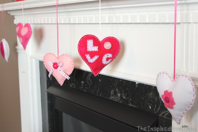 Valentine's Day Felt Hearts hung from the fireplace mantel. Tutorial available at TheInspiredHome.org